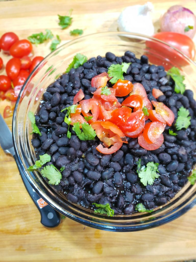 overhead image of glass bowl of cooked black beans garnished with chopped tomatoes and cilantro