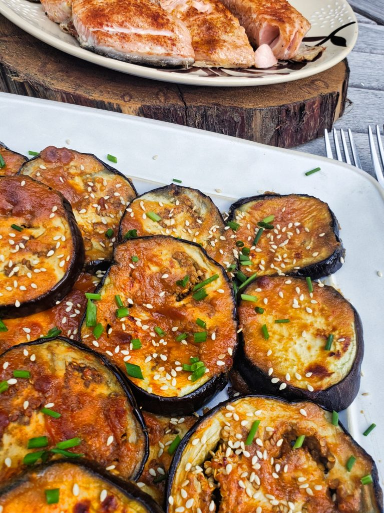 roasted eggplant glazed with miso sauce sprinkled with sesame seeds and fresh chives served with grilled salmon