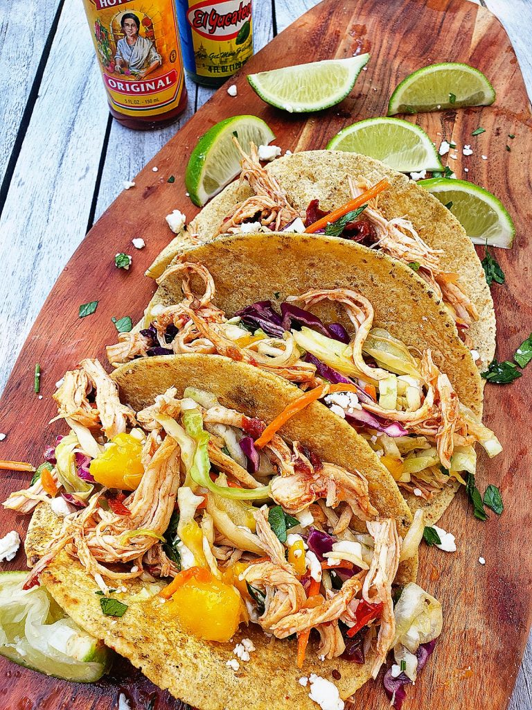 overhead side view of three chipotle chicken tacos with mango lime slaw on a wooden serving board served with lime wedges and hot sauce bottles