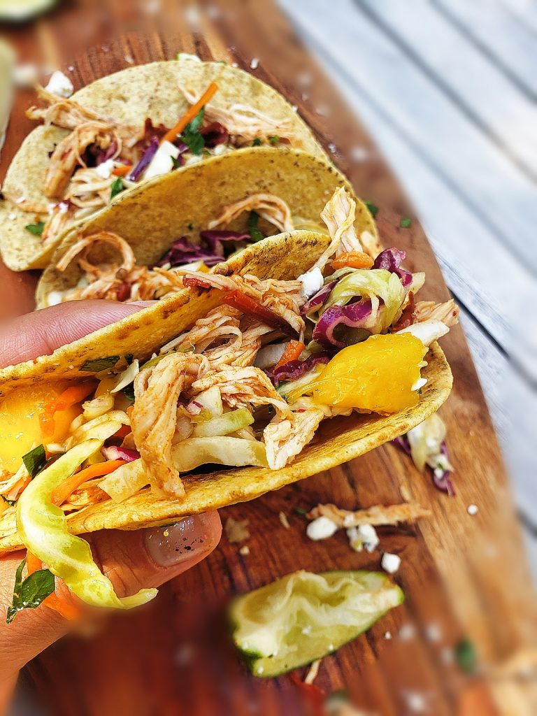 overhead view of three chipotle chicken tacos with mango slaw on a wooden board