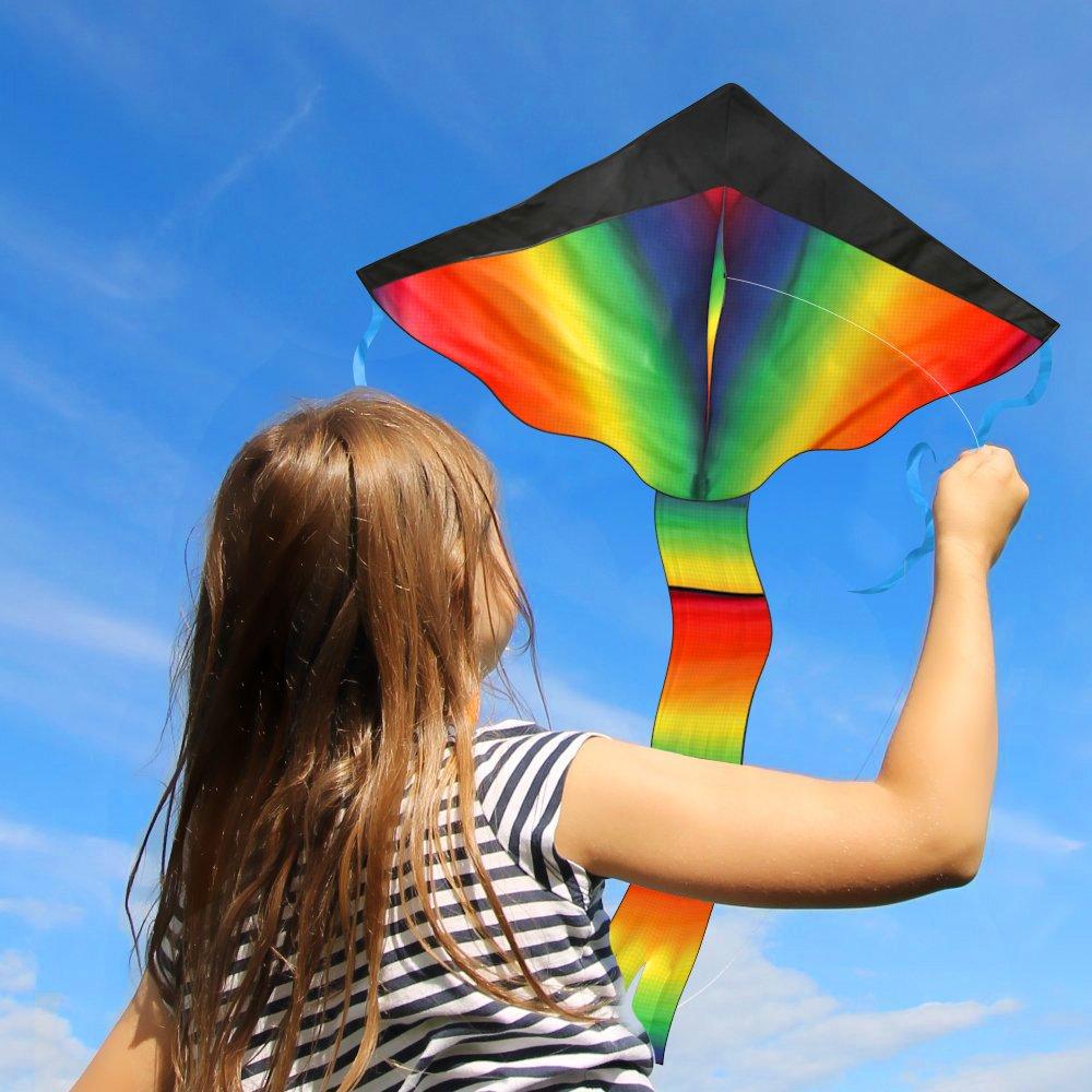 little girl flies rainbow kite in the air