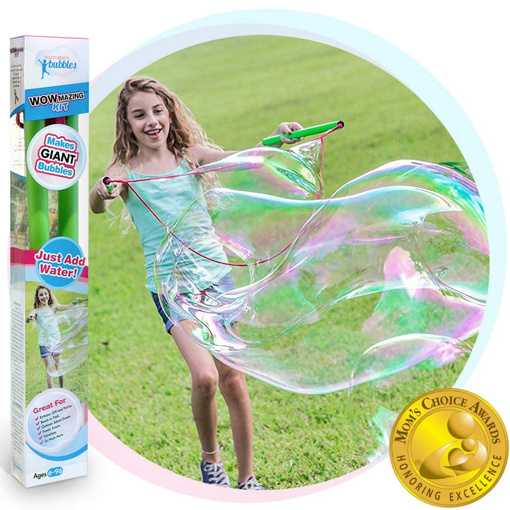 little girl makes very large bubble with wand