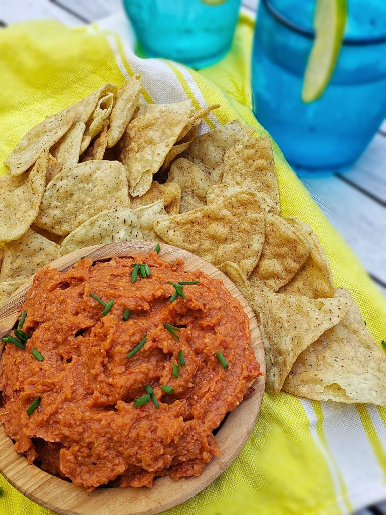 white bean chipotle dip served with tortilla chips on bright yellow linen napkin with blue tumbler glass in background
