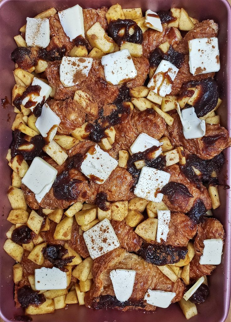 french toast in baking dish with apples, apple butter, cinnamon and butter slices