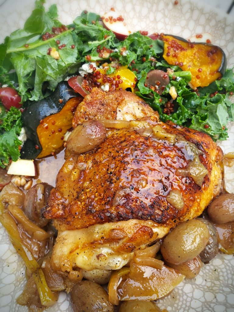 crispy cast iron seared chicken thigh with roasted grapes and apples on a plate with a kale salad