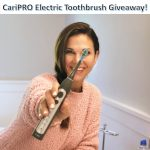 Woman showing the Cari Pro toothbrush