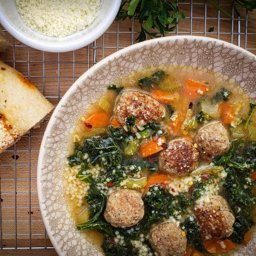 bowl of italian wedding soup with focaccia bread and grated parmesan cheese bowl
