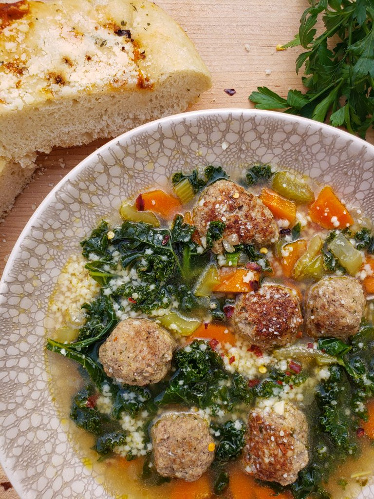 italian wedding soup with focaccia bread and parsley