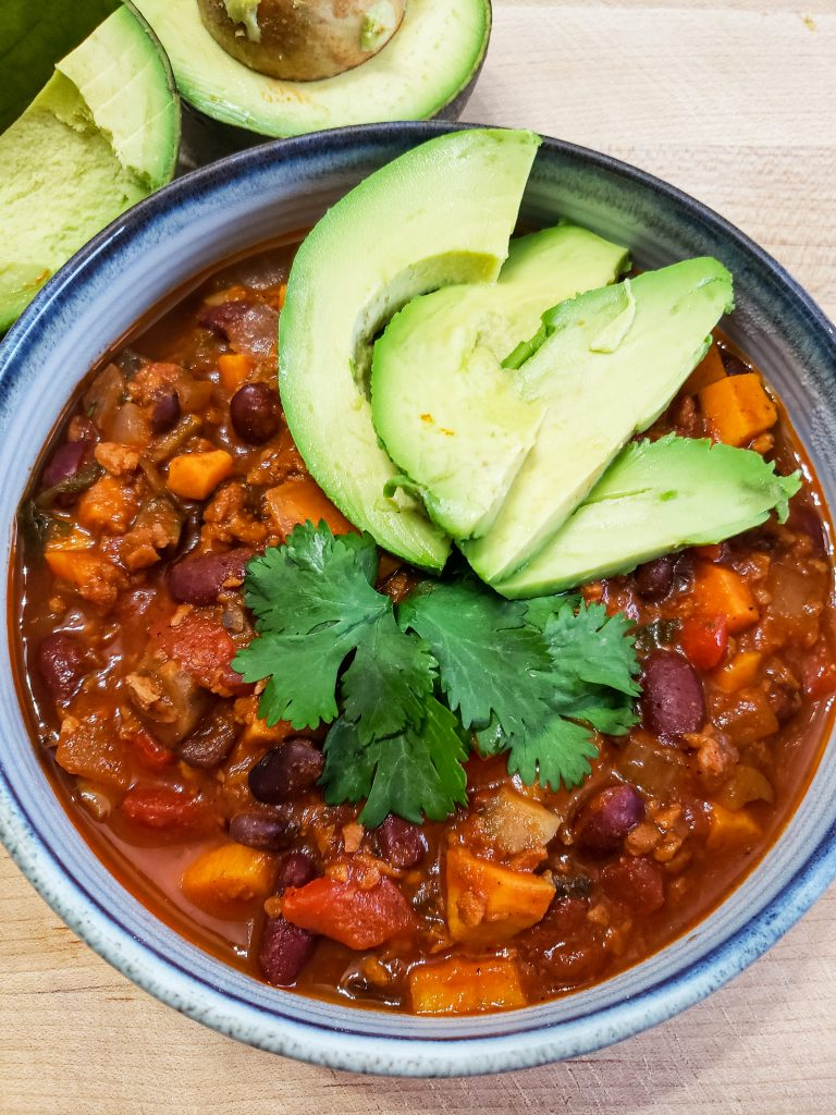 bowl of vegan chili with avocado slices and cilantro