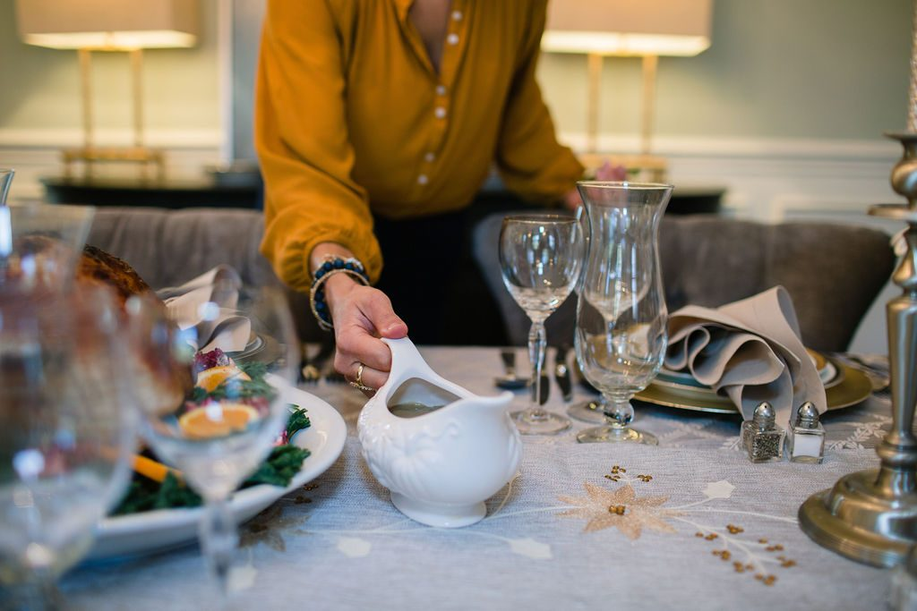 woman placing gravy boat on thanksgiving table