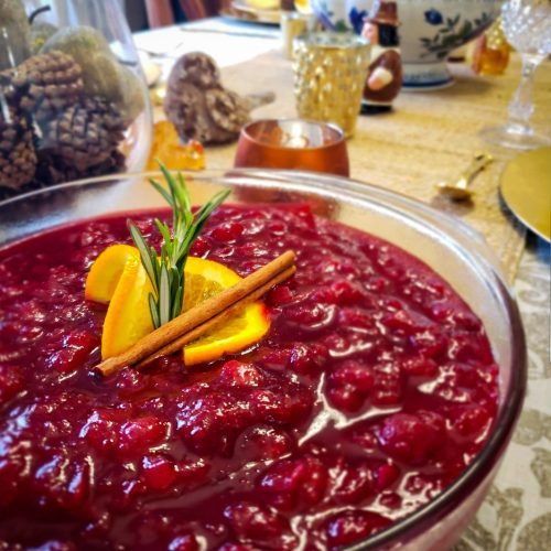 CRANBERRY SAUCE WITH APPLES AND ORANGE ZEST on thanksgiving table with orange peel , rosemary and cinnamon stick garnish