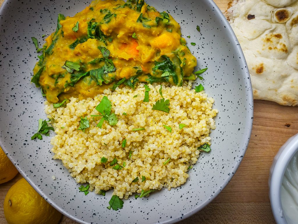 instant pot sweet potato red lentil coconut curry served with a side of quinoa and naan bread