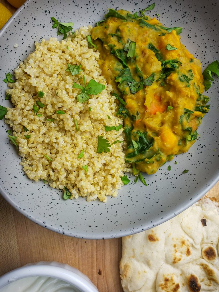 instant pot sweet potato red lentil coconut curry served with a side of quinoa