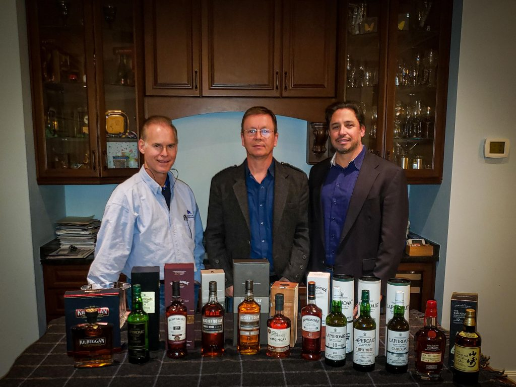 simon brookings, ken zimmerman, and lawrence lanzilli standing behind row of upscale scotch bottles