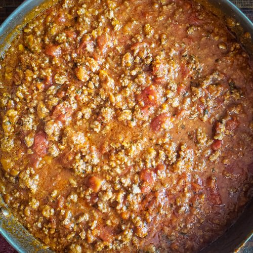 image of bolognese sauce in stainless steel pan sitting on dishtowel on table