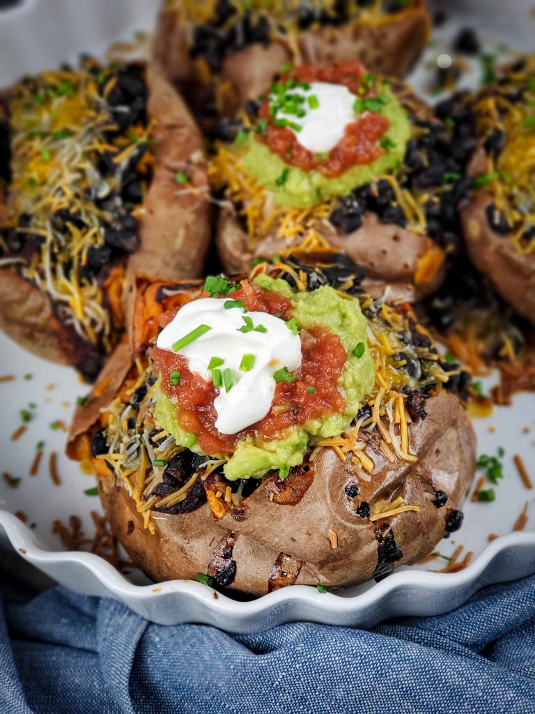 image of baking dish of black bean enchilada stuffed sweet potatoes topped with guacamole salsa and sour cream