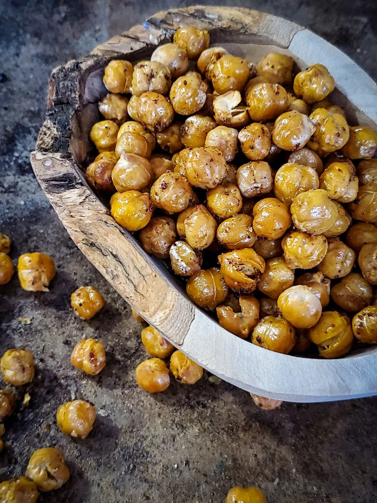 up close side angle image of wooden bowl of crisp chickpeas