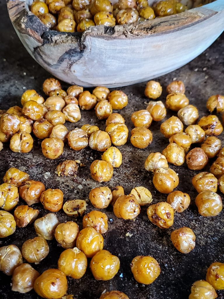 up close image of baking sheet of crispy chick peas next to a wooden bowl of chick peas