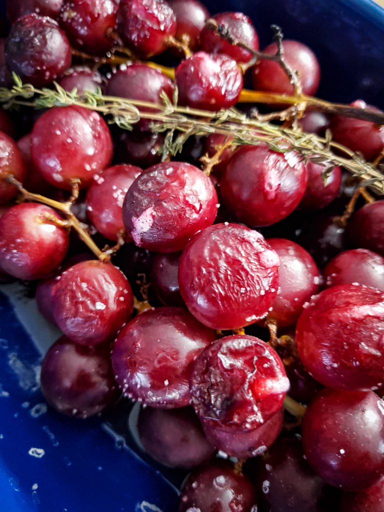 image of roasted grapes with fresh thyme sprigs on baking sheet