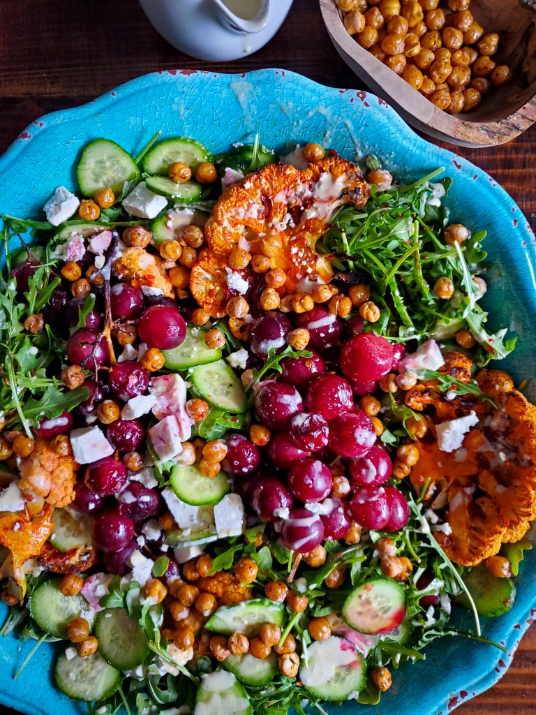 overhead image of middle eastern salad with harissa cauliflower roasted grapes and lemon tahini dressing next to wooden bowl of crispy chickpeas