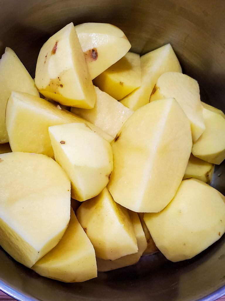 image of peeled and quartered yukon gold potatoes in pot