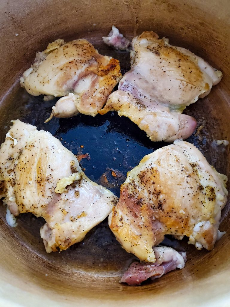 image of boneless skinless chicken thighs seared in dutch oven