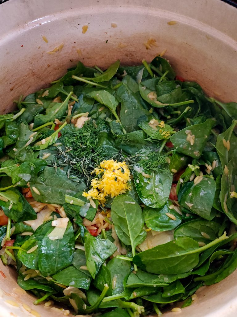 image of spinach leaves with lemon zest, fresh herbs, orzo and vegetables in dutch oven