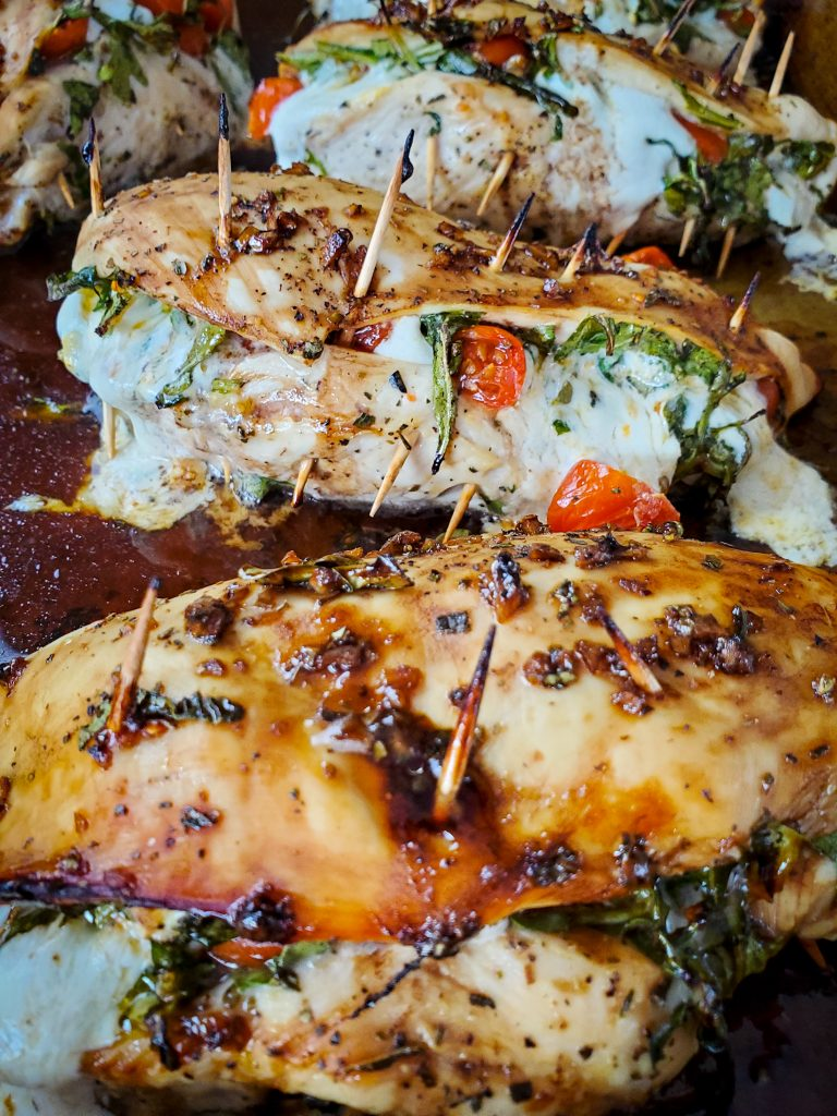 image of oven baked caprese stuffed chicken breasts with balsamic glaze secured with toothpicks