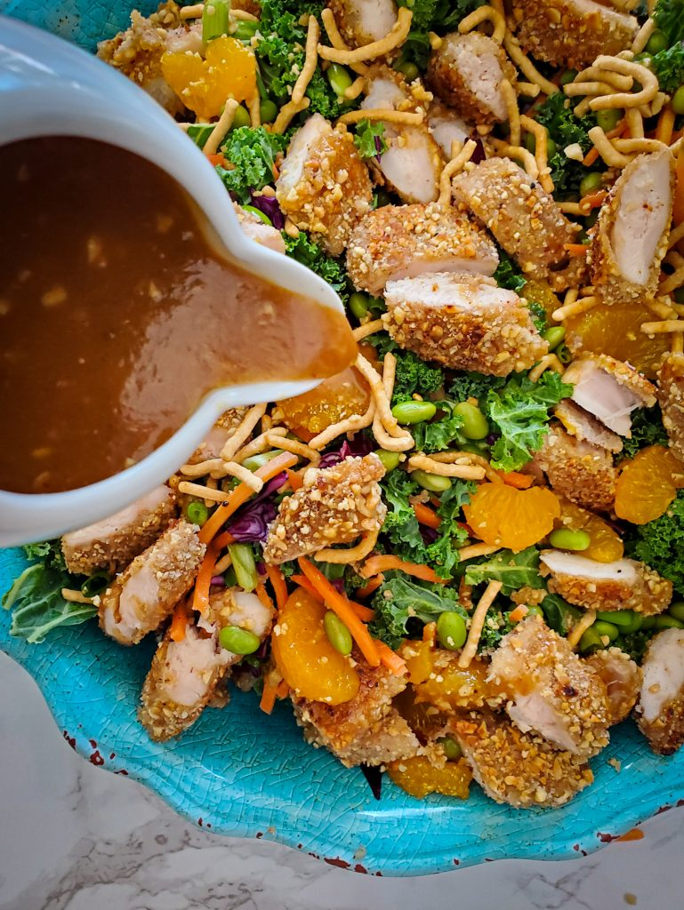 peanut ginger lime dressing poured over Chinese Salad with Peanut-Crusted Chicken Tenders