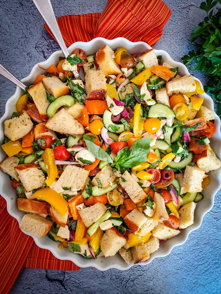 "image of large shallow bowl of ""panzanella salad"" on grey counter with red napkin and fresh herbs"