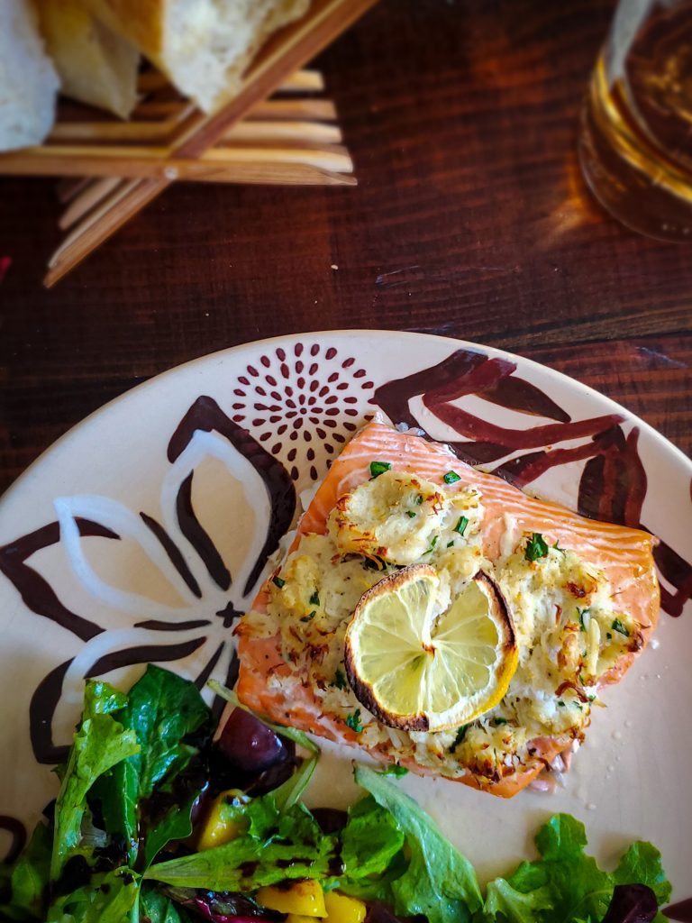 image of crab stuffed baked salmon served with salad, bread and a bottle of wine