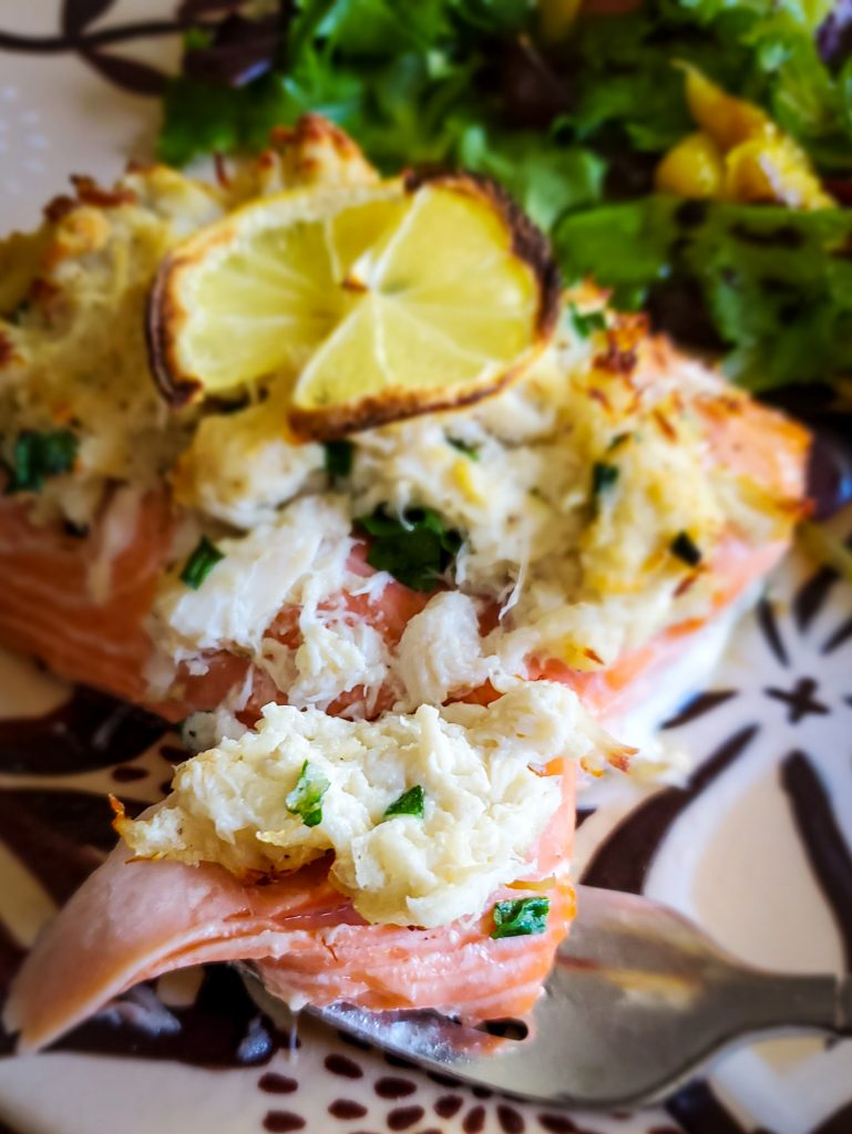 image of fork taking cutting into crab stuffed baked salmon on plate